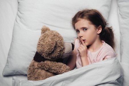 Photo pour Vue supérieure de l'enfant effrayé affichant le signe de silence et regardant l'appareil-photo tout en se trouvant dans le lit avec l'ours de nounours - image libre de droit