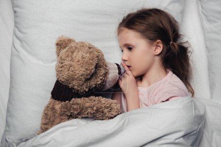 Photo pour Enfant adorable affichant le signe de silence tout en se trouvant dans le lit avec l'ours de nounours - image libre de droit