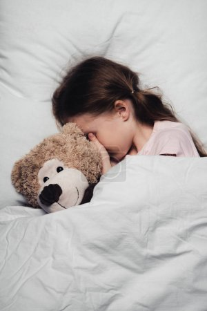 Photo for Adorable child covering eyes with hand while lying in bed with teddy bear - Royalty Free Image