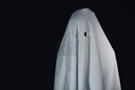 Photo pour Terrible fantôme dans drap de lit blanc isolé sur noir - image libre de droit