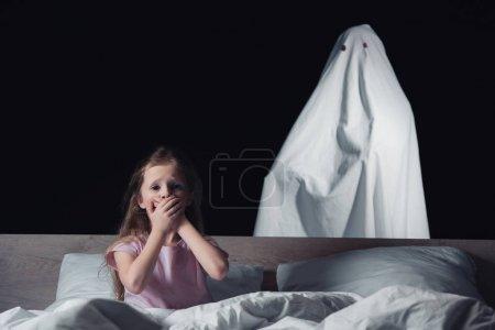 Photo pour Enfant effrayé s'asseyant dans le lit et affichant le signe de silence tandis que le fantôme blanc restant derrière le lit d'isolement sur le noir - image libre de droit