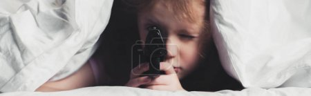 Photo for Panoramic shot of scared child holding gun while hiding under blanket - Royalty Free Image