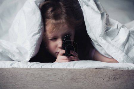 Photo for Frightened kid holding pistol while hiding under blanket in dark bedroom - Royalty Free Image