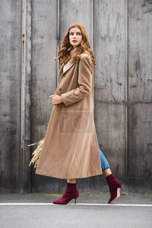 Photo for Attractive woman in coat holding spikes and looking away - Royalty Free Image
