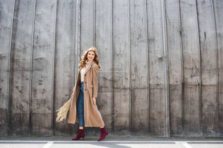 attractive and smiling woman in coat holding spikes and looking away