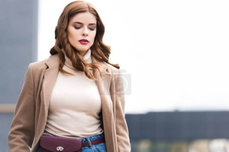 Photo for Attractive woman with closed eyes in coat and sweater - Royalty Free Image