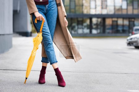 cropped view of woman in jeans holding yellow umbrella