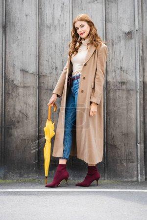 Photo pour Femme attirante dans le manteau regardant l'appareil-photo et retenant le parapluie jaune - image libre de droit