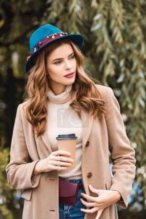 Photo pour Attrayant femme en chapeau bleu regardant loin et tenant tasse en papier - image libre de droit