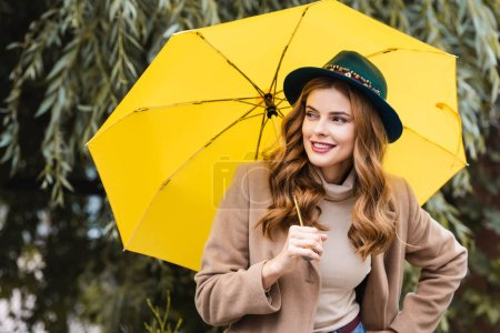 attractive woman in blue hat looking away and holding yellow umbrella