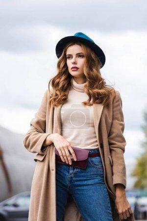 Foto de Mujer atractiva en sombrero azul y abrigo mirando hacia otro lado - Imagen libre de derechos