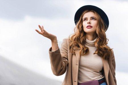 Photo pour Femme attirante dans le chapeau et le manteau bleus recherchant vers le haut - image libre de droit