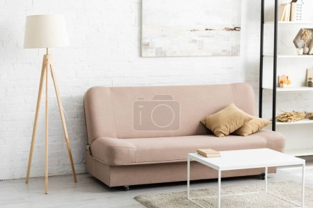 Photo for Interior of room with sofa and pillows, lamp, white table - Royalty Free Image