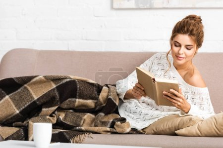 Photo for Attractive woman in white sweater sitting on sofa and reading book - Royalty Free Image