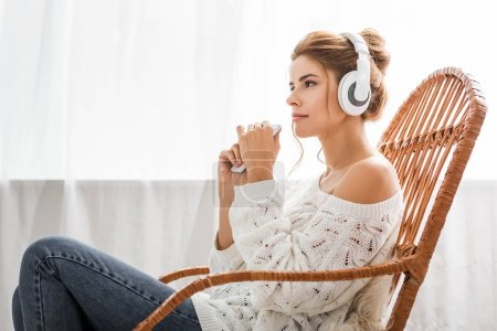 Photo pour Femme attirante dans la musique blanche d'écoute de chandail et retenant le smartphone - image libre de droit