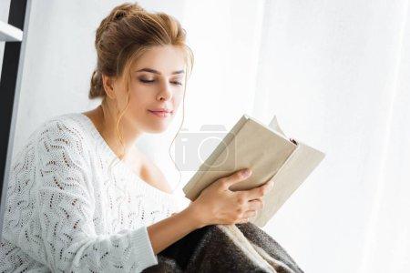 Photo pour Jolie femme en pull blanc avec couverture livre de lecture - image libre de droit
