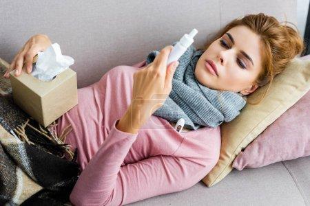 Photo pour Femme attrayante et malade avec écharpe grise tenant gouttes de nez - image libre de droit