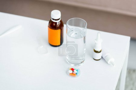 Photo for High angle view of nose drops, cough syrup, pills and glass of water - Royalty Free Image