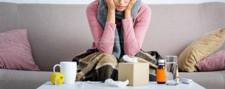 Photo pour Prise de vue panoramique de la femme malade avec écharpe grise assise sur le canapé - image libre de droit