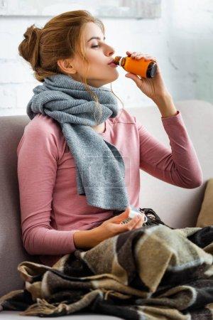 Foto de Mujer atractiva y enferma con bufanda gris beber jarabe para la tos - Imagen libre de derechos