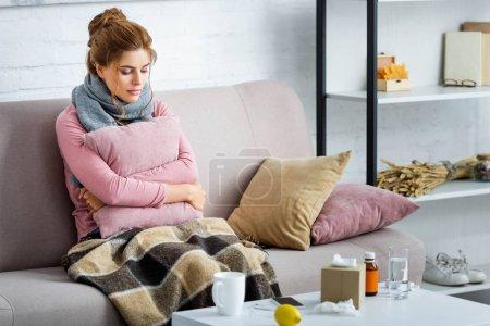 Photo pour Femme attrayante et malade avec écharpe grise assise sur le canapé et tenant oreiller - image libre de droit