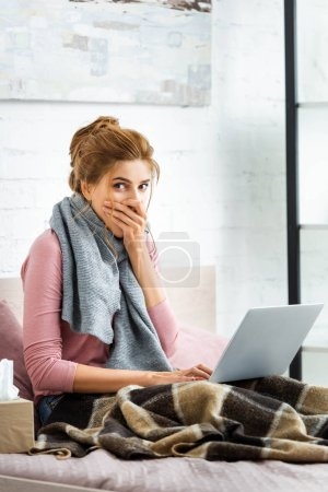 Photo for Attractive and shocked woman with grey scarf holding laptop - Royalty Free Image