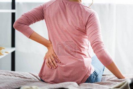 Photo pour Vue arrière de la femme avec douleur dans le dos assis sur le lit dans l'appartement - image libre de droit