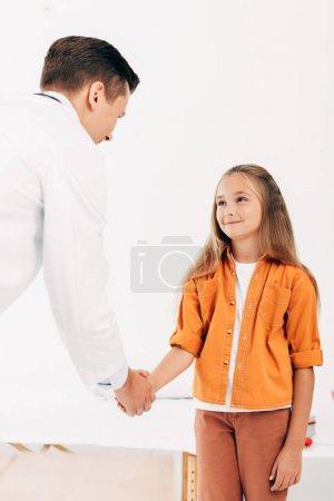 Photo pour Pédiatre en manteau blanc et enfant serrant la main et se regardant - image libre de droit