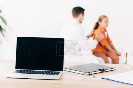 Photo for Selective focus of pediatrist examining child and laptop with blank screen on foreground - Royalty Free Image