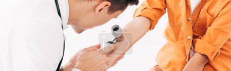 panoramic shot of pediatrist examining child with dermascope isolated on white