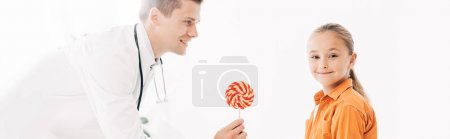 Photo for Panoramic shot of pediatrist giving candy to child on white - Royalty Free Image
