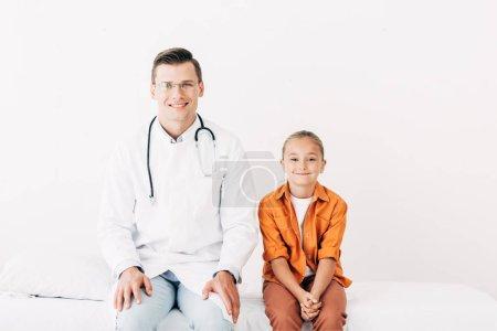 Photo pour Vue avant du pédiatre de sourire dans le manteau blanc et l'enfant s'asseyant sur le bâti d'hôpital dans la clinique - image libre de droit