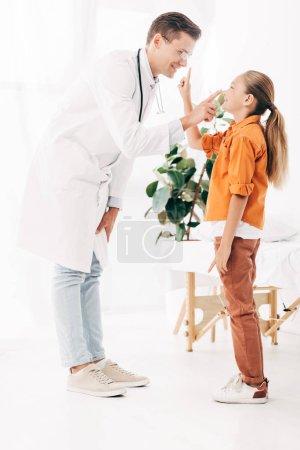 Photo pour Vue complète du pédiatre souriant en manteau blanc et de l'enfant à la clinique - image libre de droit