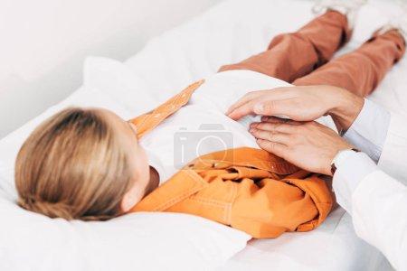 Photo pour Vue partielle du pédiatre en blouse blanche examinant l'enfant à la clinique - image libre de droit