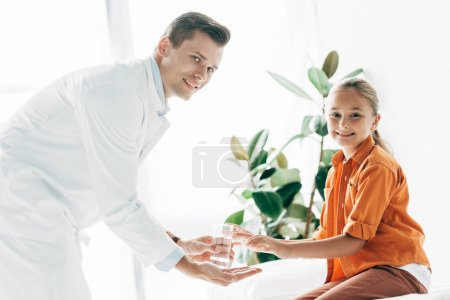 smiling pediatrist in white coat giving glass of water to child in clinic
