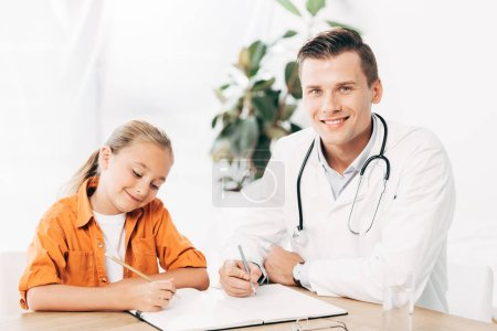 Photo for Smiling child and pediatrist writing in notebook at table in clinic - Royalty Free Image