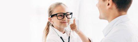 Photo pour Plan panoramique d'enfant souriant en costume de médecin regardant le patient et montrant pouce vers le haut - image libre de droit