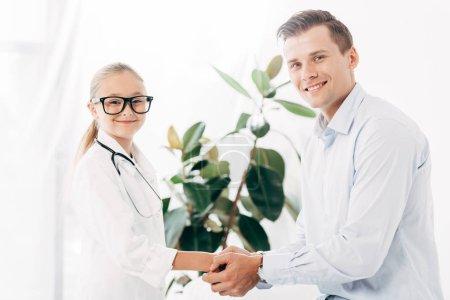 Photo pour Gosse de sourire dans le costume de docteur retenant des mains avec le patient - image libre de droit