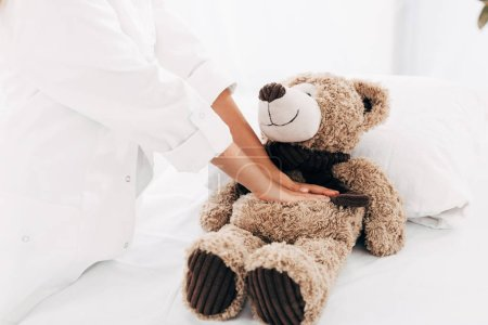 Photo for Partial view of kid in doctor costume doing heart massage to teddy bear - Royalty Free Image