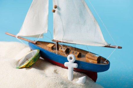 Photo pour Bateau miniature près de la boussole et de l'ancre dans le sable blanc d'isolement sur le bleu - image libre de droit