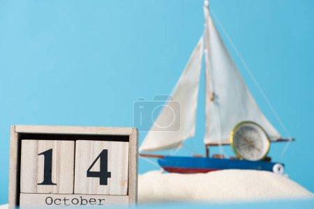 Photo pour Calendrier en bois avec date du 14 octobre près du navire décoratif et de la boussole dans le sable blanc isolé sur le bleu - image libre de droit