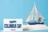"""Постер, картина, фотообои """"карта со счастливым Днем Колумба надпись возле миниатюрного корабля в белом песке изолированы на синем"""""""