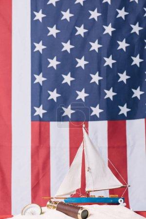 Photo pour Navire décoratif dans le sable blanc près de la boussole et du télescope sur le fond national américain de drapeau - image libre de droit