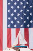 """Постер, картина, фотообои """"декоративный корабль в белом песке возле компаса и телескопа на фоне американского национального флага"""""""
