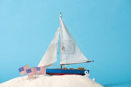 Photo pour Navire décoratif près des drapeaux nationaux américains dans le sable blanc d'isolement sur le bleu - image libre de droit