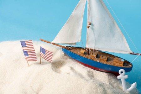 Photo pour Indicateurs nationaux américains dans le sable blanc près du bateau miniature et de l'ancre d'isolement sur le bleu - image libre de droit