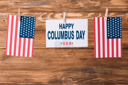 Photo for Card with happy Columbus day inscription between American national flags on wooden surface - Royalty Free Image