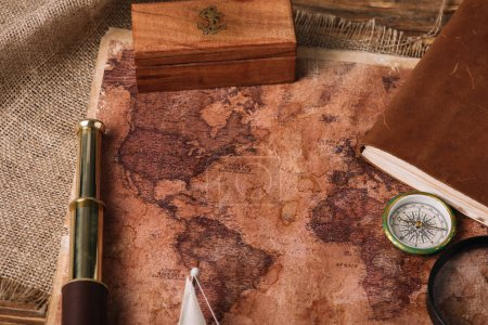 wooden box, telescope, compass and aged world map on hessian