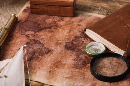 Foto de Viejo mapa del mundo cerca del telescopio, cuaderno de cuero y la brújula en Hessian - Imagen libre de derechos
