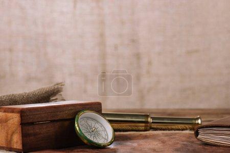 Photo pour Boîte en bois brun près boussole et télescope doré et morceau de sac - image libre de droit